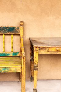 Old New Mexico porch (portale) with rustic wood bench, table, and traditional dun-colored adobe stucco.